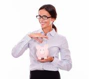 Uśmiechnięty bizneswomanu mienia menchii prosiątka bank Fotografia Stock