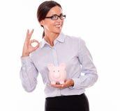 Uśmiechnięty bizneswomanu mienia menchii prosiątka bank Fotografia Royalty Free
