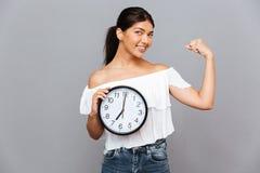 Uśmiechnięty bizneswomanu mienie zegarowy i seansów bicepsy Fotografia Royalty Free