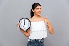 Uśmiechnięty bizneswomanu mienie zegarowy i seansu kciuk up Zdjęcie Stock