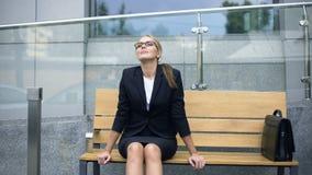 Uśmiechnięty bizneswomanu obsiadanie na ławce, relaksuje po stresującego pracującego dnia zdjęcie wideo