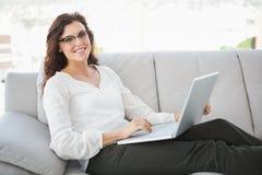 Uśmiechnięty bizneswomanu obsiadanie na kanapie używać laptop Obrazy Stock