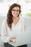 Uśmiechnięty bizneswomanu obsiadanie na leżance używać laptop Fotografia Stock