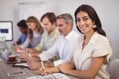 Uśmiechnięty bizneswomanu writing na papierze z kolegami w sala konferencyjnej obraz stock