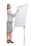 Uśmiechnięty bizneswomanu writing na trzepnięcie desce Obraz Stock