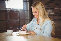 Uśmiechnięty blondynki łasowanie tortowy i ma kawę Obraz Royalty Free