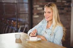 Uśmiechnięty blondynki łasowanie tortowy i ma kawę Obrazy Stock