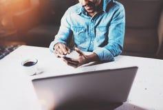 Uśmiechnięty brodaty Afrykański biznesmen używa telefon przy drewnianym stołem na jego nowożytnym domu podczas gdy siedzący Pojęc obrazy stock