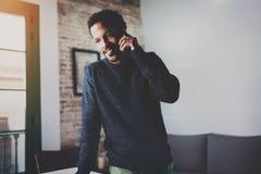 Uśmiechnięty brodaty Afrykański mężczyzna opowiada na smartphone podczas gdy stojący blisko okno w jego nowożytnym mieszkaniu Poj zdjęcia royalty free