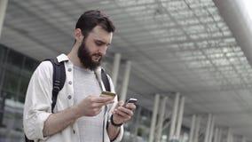 Uśmiechnięty brodaty mężczyzna chodzi z plecakiem i sprawdza jego kredytową kartę zbiory wideo