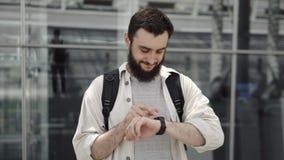 Uśmiechnięty brodaty mężczyzna chodzi z plecakiem i sprawdza jego mądrze zegarek zbiory