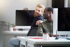 Uśmiechnięty brodaty mężczyzna dostaje uwagę jego męski kolega obraz stock