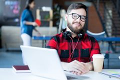 Uśmiechnięty Brodaty mężczyzna w IT biurze zdjęcie royalty free