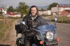 Uśmiechnięty brodaty rowerzysta w czarnym skórzanej kurtki obsiadaniu na nowożytnym motocyklu na kraju poboczu zdjęcia royalty free