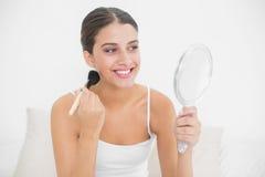 Uśmiechnięty brown z włosami model w białych piżamach stosuje proszek na jej twarzy Obraz Stock