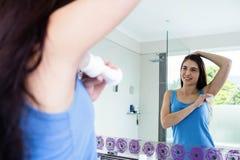 Uśmiechnięty brunetki kładzenia dezodorant na jej pasze obraz stock