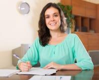Uśmiechnięty brunetki kobiety czytania dokument Zdjęcia Stock