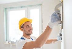 Uśmiechnięty budowniczy pracuje z śrutowania narzędziem indoors Zdjęcia Stock