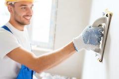 Uśmiechnięty budowniczy z śrutowania narzędziem indoors Zdjęcia Stock