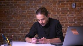Uśmiechnięty caucasian biznesmen zatrzymywał jego patrzejącego smartphone z wygranie gestem w ceglanym studiu i pracę