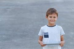 Uśmiechnięty chłopiec chwyta pastylki pecet Szkoła, edukacja, uczenie, technologia, czasu wolnego pojęcie Fotografia Stock