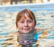 Uśmiechnięty chłopiec dopłynięcie w basenie fotografia stock