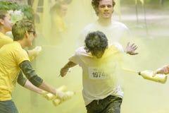 Uśmiechnięty chłopiec dostawać obsikiwał z żółtym koloru pyłem w ich fa Fotografia Stock