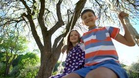 Uśmiechnięty chłopiec i dziewczyny chlanie na huśtawce w wiośnie Mi?o?ci najpierw poj?cie zdjęcie wideo