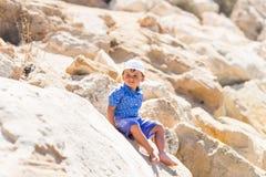 Uśmiechnięty chłopiec obsiadanie na skale Zdjęcia Stock
