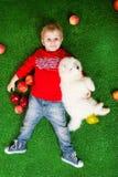 Uśmiechnięty chłopiec trzy lat kłaść z białym szczeniakiem obraz royalty free