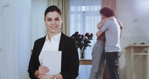 Uśmiechnięty charyzmatyczny domowy agent patrzeje prosty przed kamerą podczas gdy na tylnej atrakcyjnej potomstwo parze jest zbiory