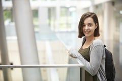 Uśmiechnięty ciemny z włosami żeński uczeń w uniwersyteckim budynku obrazy stock