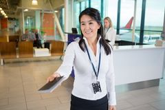 Uśmiechnięty członel personelu Daje paszportowi Przy Lotniskowym Terminal Obrazy Royalty Free