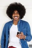 Uśmiechnięty czarny facet słucha muzyka na mądrze telefonie obrazy royalty free