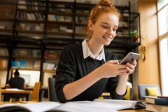 Uśmiechnięty czerwony z włosami nastoletniej dziewczyny studiowanie przy stołem fotografia royalty free