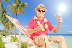 Uśmiechnięty dżentelmenu obsiadanie na plażowego krzesła i mienia dolarze amerykańskim Obraz Royalty Free