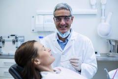 Uśmiechnięty dentysta egzamininuje pacjenta z narzędziami zdjęcia stock