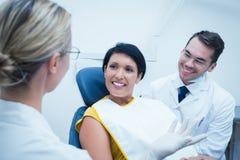 Uśmiechnięty dentysta i asystent z żeńskim pacjentem Zdjęcie Royalty Free