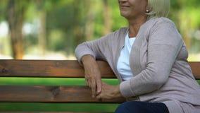 Uśmiechnięty dojrzały damy obsiadanie w parku, zadowolonym z jej życiem, emerytalna reforma zbiory