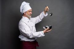 Uśmiechnięty dojrzały męski szef kuchni z pucharem i kulinarnym vane w rękach na czarnym tle zdjęcia stock