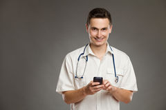 Uśmiechnięty doktorski pozować z telefonem komórkowym Zdjęcia Royalty Free