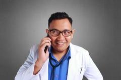 Uśmiechnięty Doktorski wyrażenie Opowiada Na telefonie zdjęcia stock