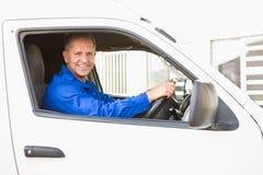 Uśmiechnięty doręczeniowy mężczyzna jedzie jego samochód dostawczego Obraz Stock