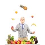 Uśmiechnięty dorośleć mężczyzna kuglarskie owoc za stołem folującym z fr Obraz Royalty Free