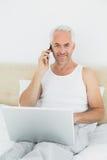 Uśmiechnięty dorośleć mężczyzna używa telefon komórkowego i laptop w łóżku Fotografia Royalty Free