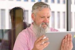 Uśmiechnięty dorośleć mężczyzna z długą brodą używać pastylkę zdjęcia royalty free