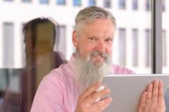 Uśmiechnięty dorośleć mężczyzna z długą brodą używać pastylkę obraz royalty free