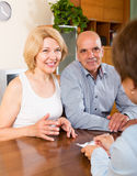 Uśmiechnięty dorośleć pary emeryci opowiada z pracownikiem Zdjęcia Royalty Free