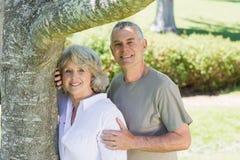 Uśmiechnięty dorośleć pary oprócz drzewa przy parkiem Zdjęcia Royalty Free