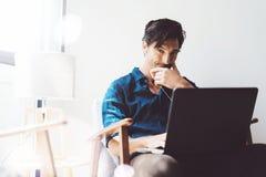 Uśmiechnięty dorosły biznesmen pracuje przy biurem Obsługuje używać współczesnego notatnika na hełmofonach w rocznika krześle pod Zdjęcie Royalty Free